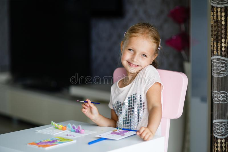 Leuk Meisje met blondehaar het Schilderen Beeld thuis Terug naar school, onderwijs, homeschoolconcept royalty-vrije stock afbeeldingen