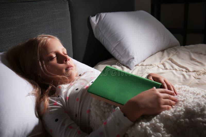 Leuk meisje met boekslaap in bed thuis royalty-vrije stock foto