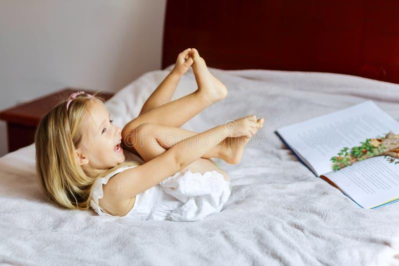 Leuk meisje met de lezingsboek van het blondehaar op het bed stock fotografie