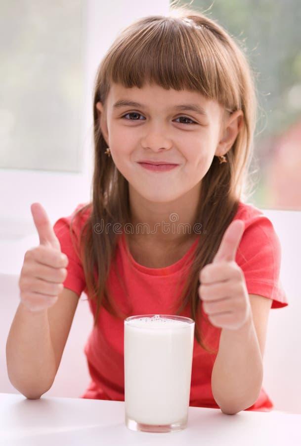 Leuk meisje met een glas melk stock afbeeldingen
