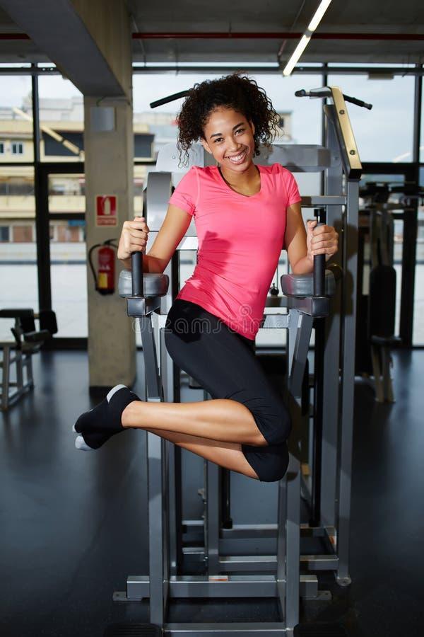 Leuk meisje met een mooie glimlach die voor abs spieren uitwerken bij gymnastiek stock foto's