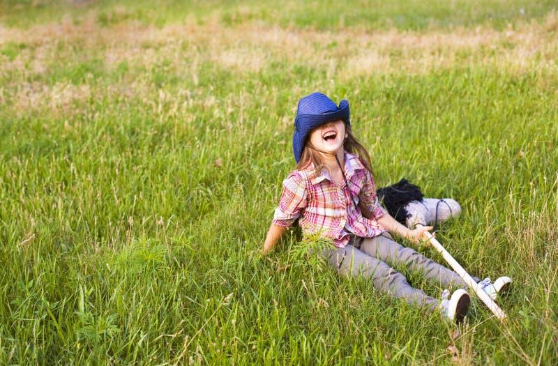 Leuk meisje met een stuk speelgoed paardpret in openlucht royalty-vrije stock fotografie