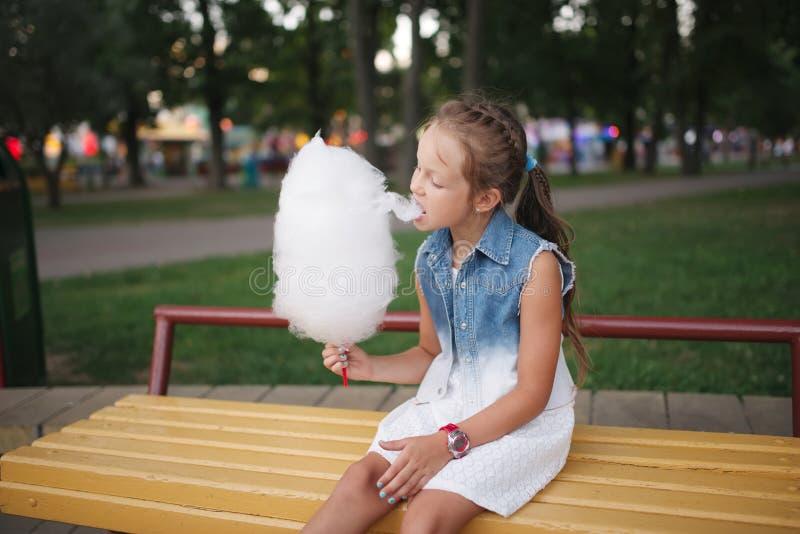 Leuk meisje met gesponnen suiker in park stock afbeeldingen