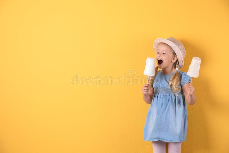 Leuk meisje met gesponnen suikers op kleurenachtergrond stock foto