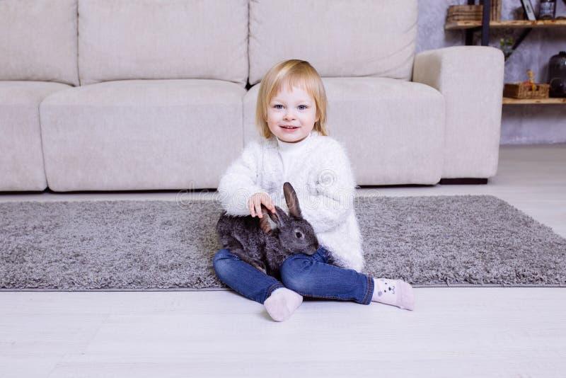 Leuk meisje met grijs Pasen-konijn, konijntje Het meisje van de blondebaby in witte sweater glimlachen en jeans die thuis op c zi stock afbeeldingen