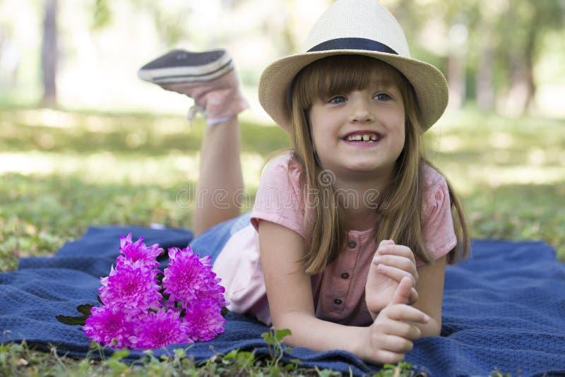 Leuk meisje met grote blauwe ogen met een hoed die op een blanke liggen royalty-vrije stock foto