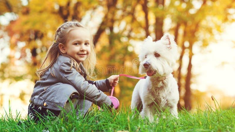 Leuk meisje met haar hond in de herfstpark Mooi kind die met hond in gevallen bladeren lopen Modieus meisje die colourf genieten  royalty-vrije stock fotografie