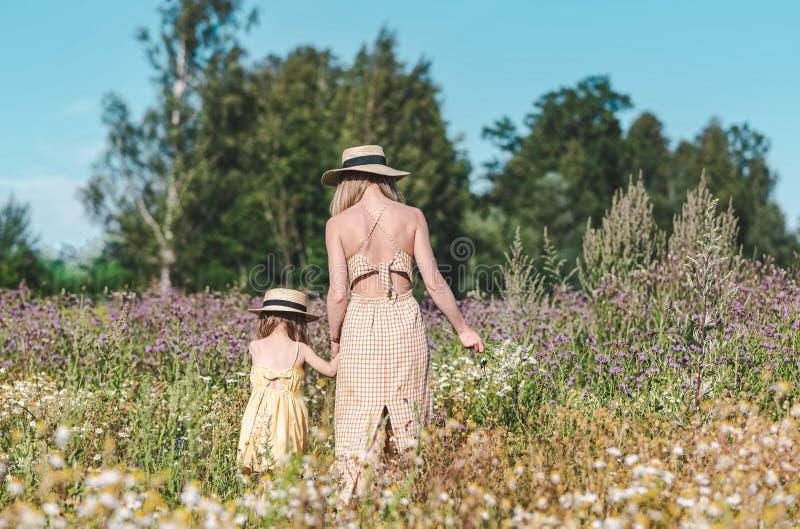 Leuk meisje met haar moeder die op het bloemengebied lopen royalty-vrije stock fotografie