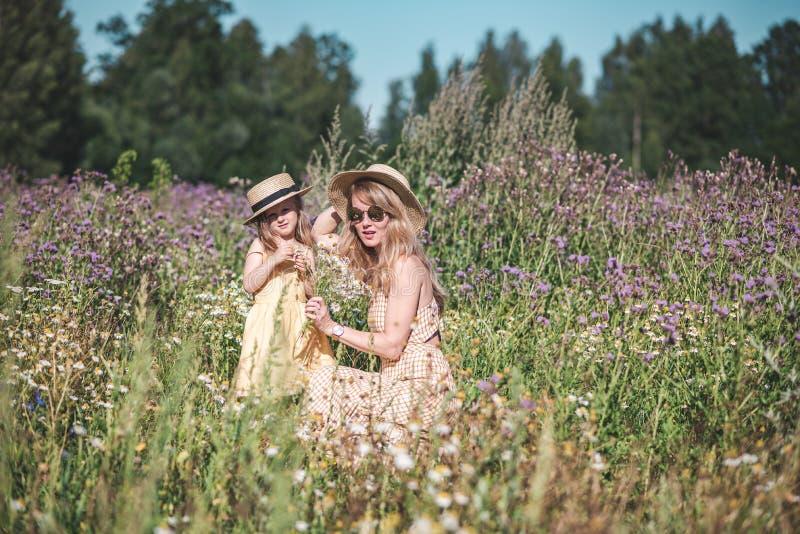 Leuk meisje met haar moeder die op het bloemengebied lopen royalty-vrije stock afbeelding