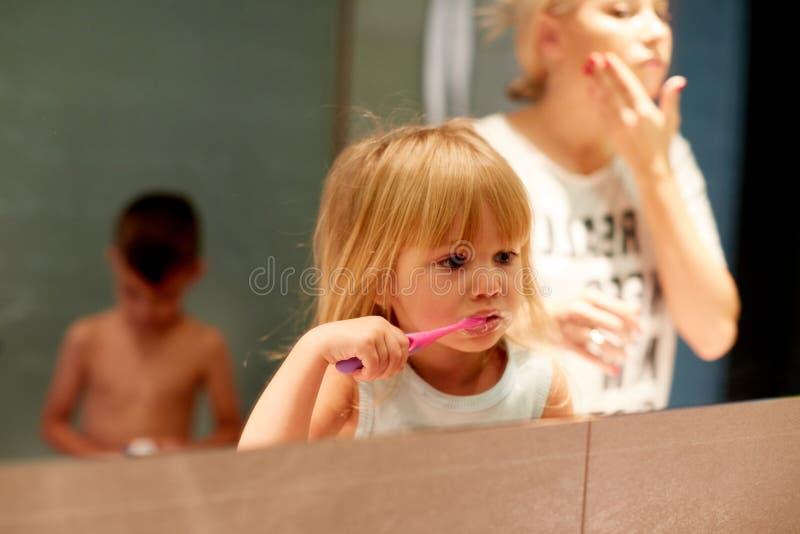 Leuk meisje met haar moeder het borstelen tanden dichtbij spiegel in badkamers stock fotografie