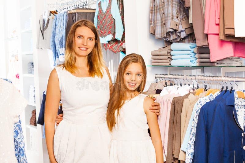 Leuk meisje met haar moeder in witte uitrusting bij winkel royalty-vrije stock afbeelding