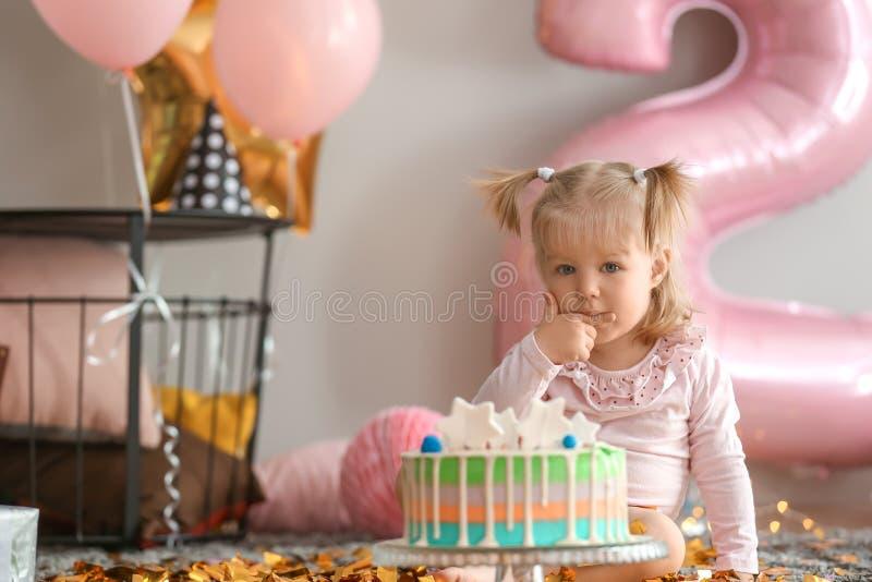 Leuk meisje met heerlijke cakezitting op tapijt in ruimte die voor verjaardagspartij wordt verfraaid stock afbeeldingen