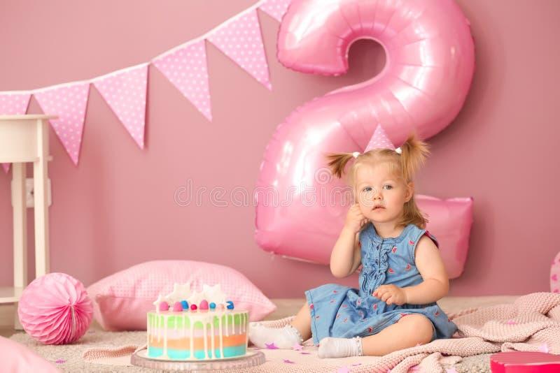 Leuk meisje met heerlijke cakezitting op tapijt in ruimte die voor verjaardagspartij wordt verfraaid stock foto