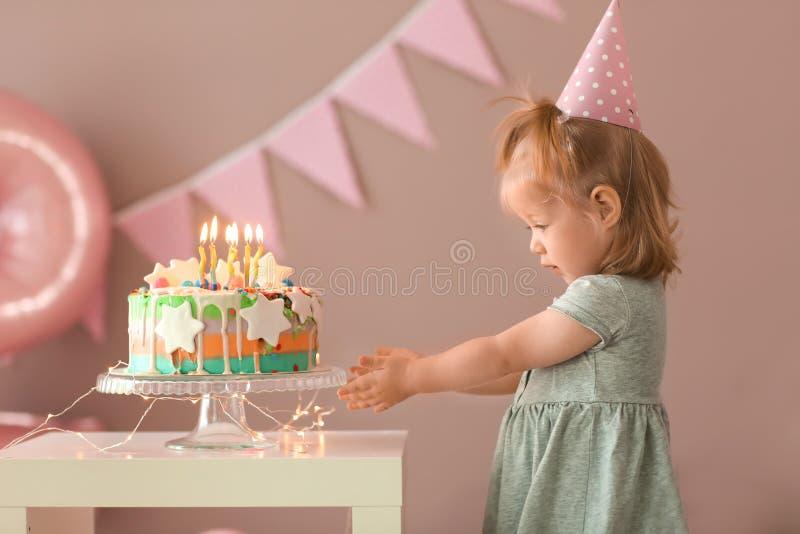 Leuk meisje met heerlijke die cake in ruimte voor verjaardagspartij wordt verfraaid royalty-vrije stock foto