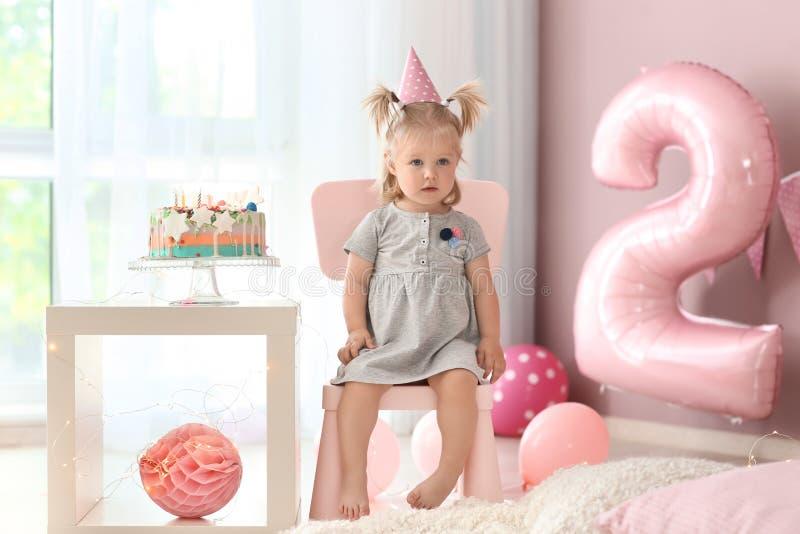 Leuk meisje met heerlijke die cakezitting op stoel in ruimte voor verjaardagspartij wordt verfraaid royalty-vrije stock foto