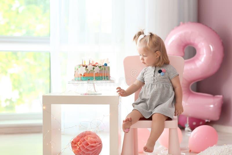 Leuk meisje met heerlijke die cakezitting op stoel in ruimte voor verjaardagspartij wordt verfraaid stock foto's