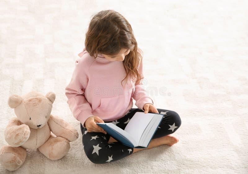 Leuk meisje met het boek van de teddybeerlezing op vloer stock afbeeldingen