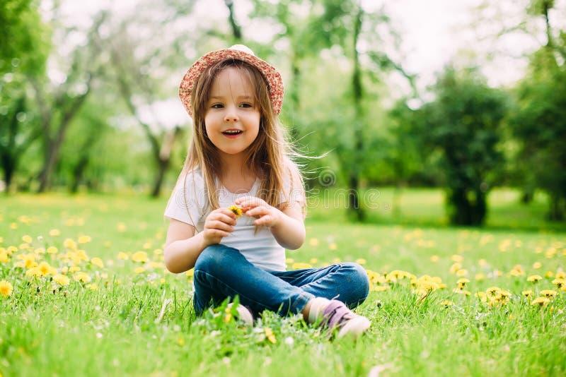 Leuk meisje met hoed die op het gras situeren stock afbeeldingen
