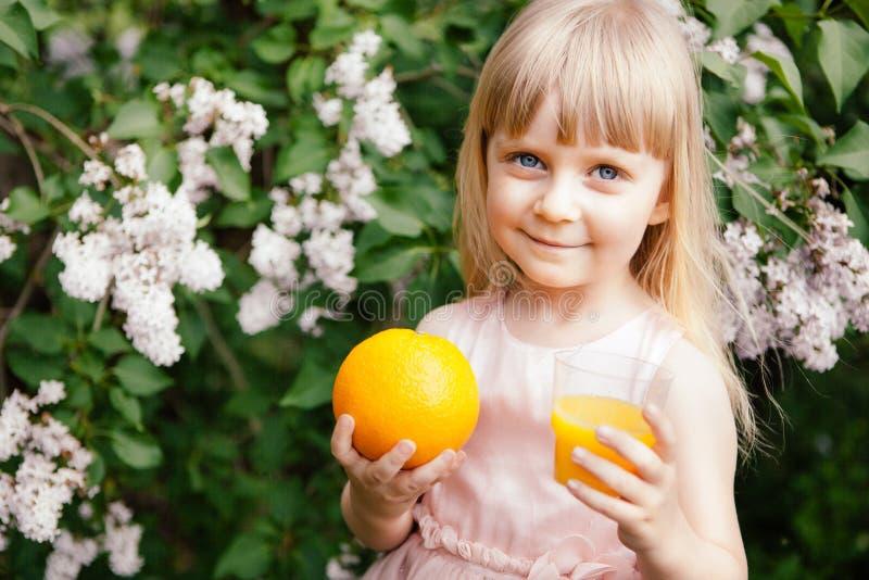 Leuk meisje met jus d'orange en oranje fruit, gezonde drank stock foto