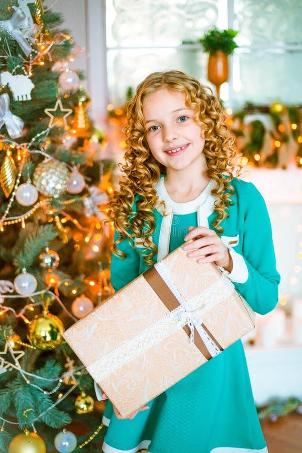 Leuk meisje met krullend blond haar thuis dichtbij een Kerstboom met giften en slingers en een verfraaide open haard stock afbeeldingen