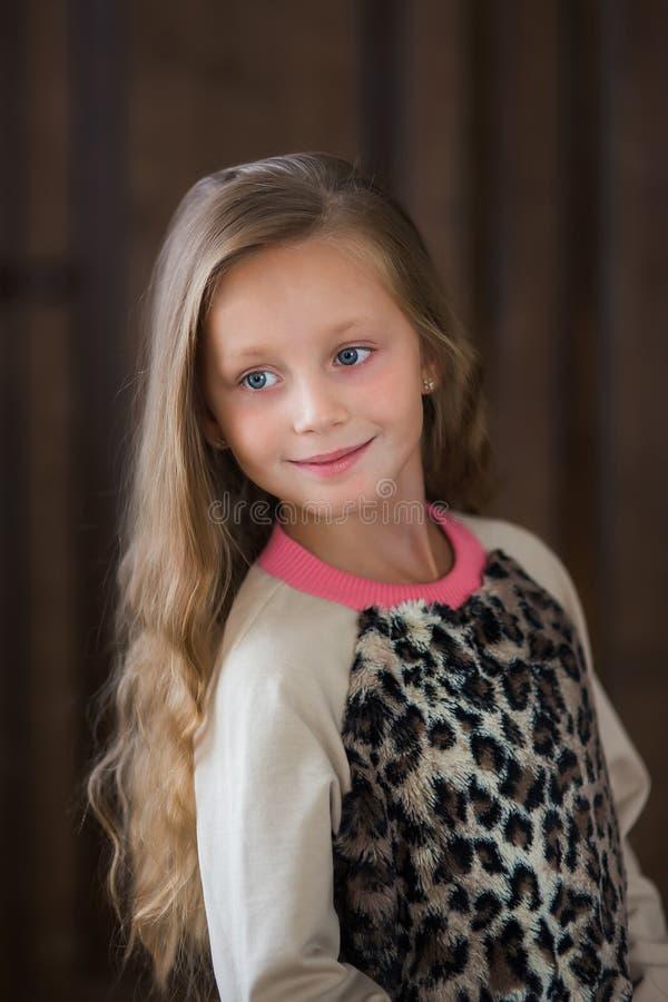 Leuk meisje met lang haar op een bruin close-up als achtergrond stock afbeelding