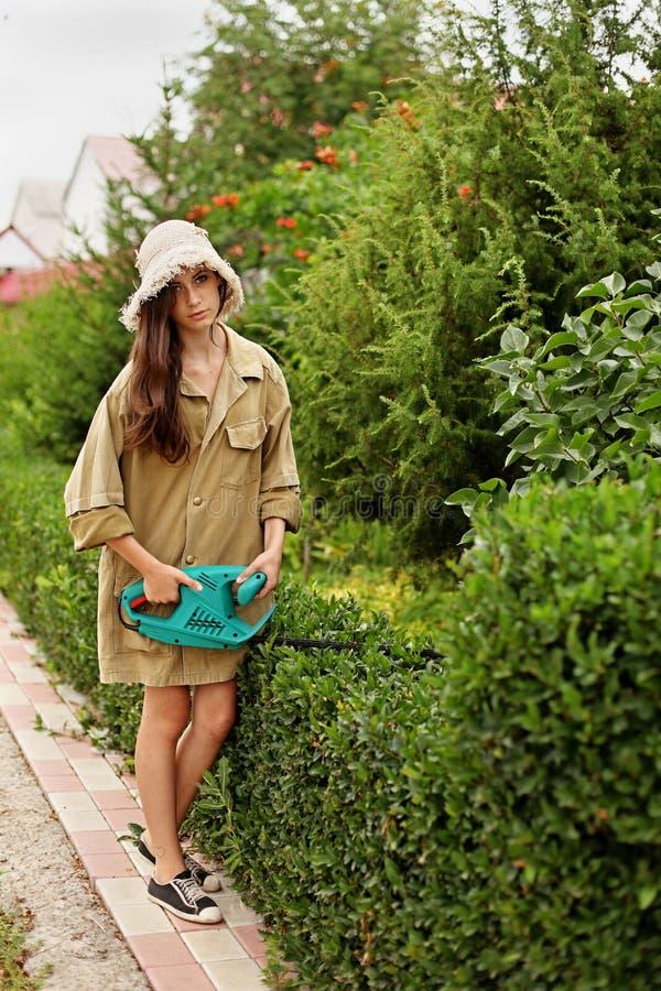Leuk meisje met lang haar scherp bukshout met elektrohaagsnoeischaar royalty-vrije stock foto's