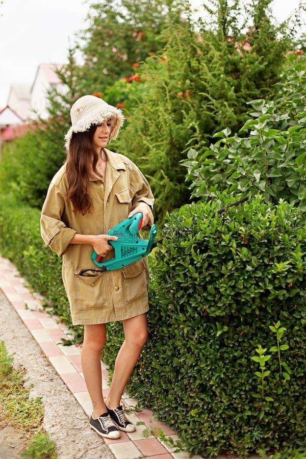 Leuk meisje met lang haar scherp bukshout met elektrohaagsnoeischaar stock fotografie