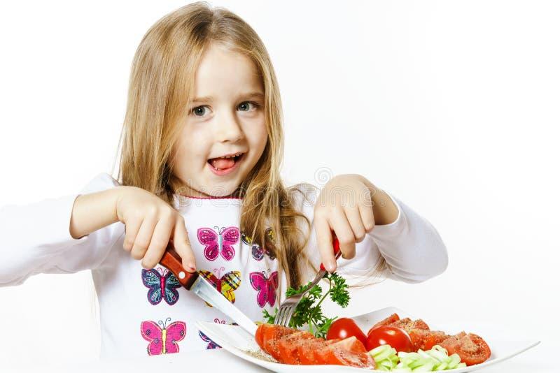 Leuk meisje met plaat van verse groenten stock fotografie