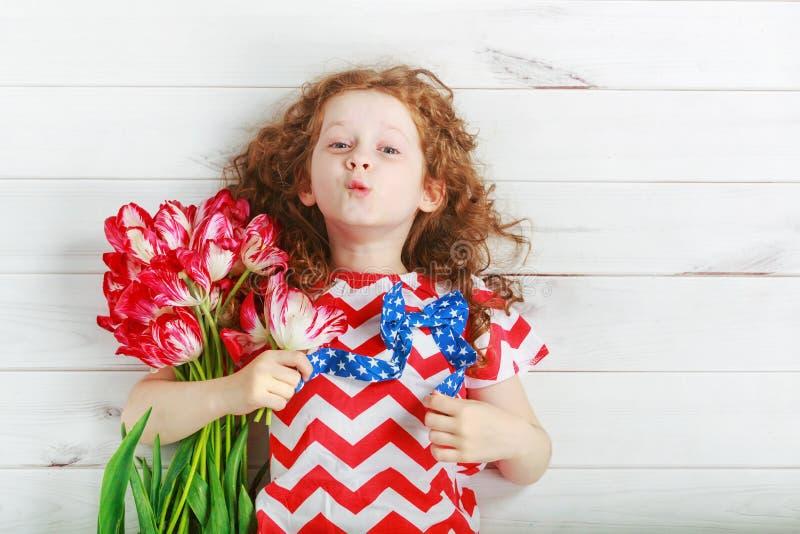 Leuk meisje met rode tulpen bij het vieren van 4 juli Indepe royalty-vrije stock afbeeldingen