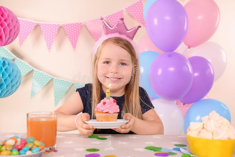 Leuk meisje met smakelijke cupcake het vieren Verjaardag thuis stock afbeelding