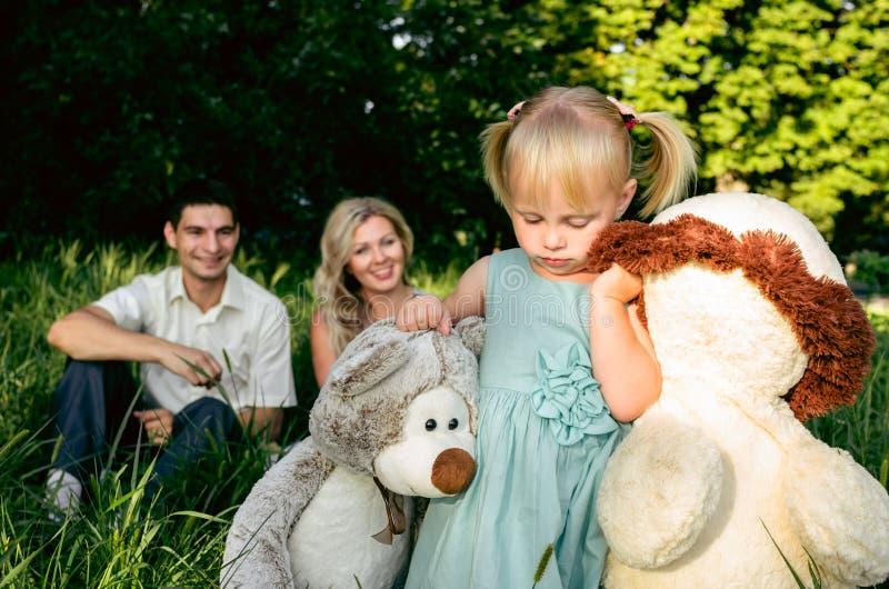 Leuk meisje op een weide op een de zomerdag met mamma en papa stock foto's