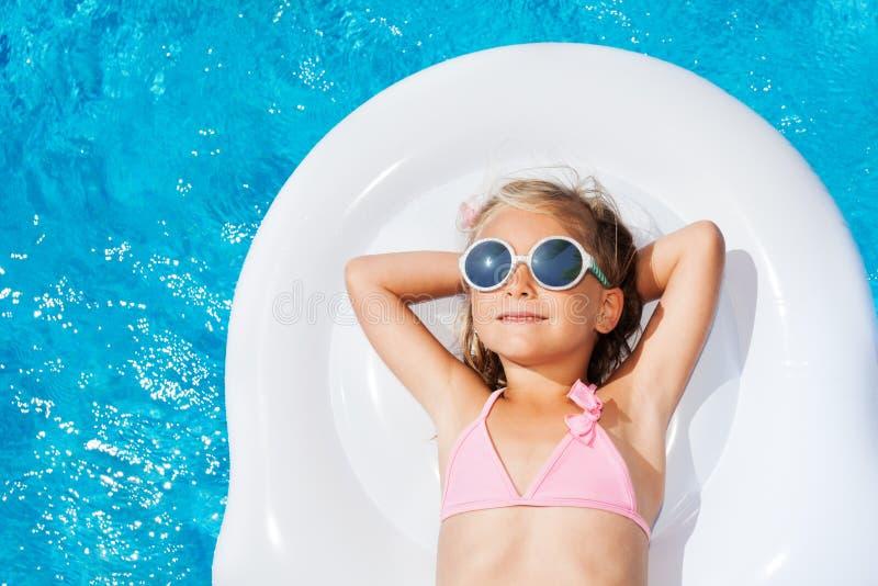 Leuk meisje op opblaasbare matras in zwembad royalty-vrije stock afbeeldingen