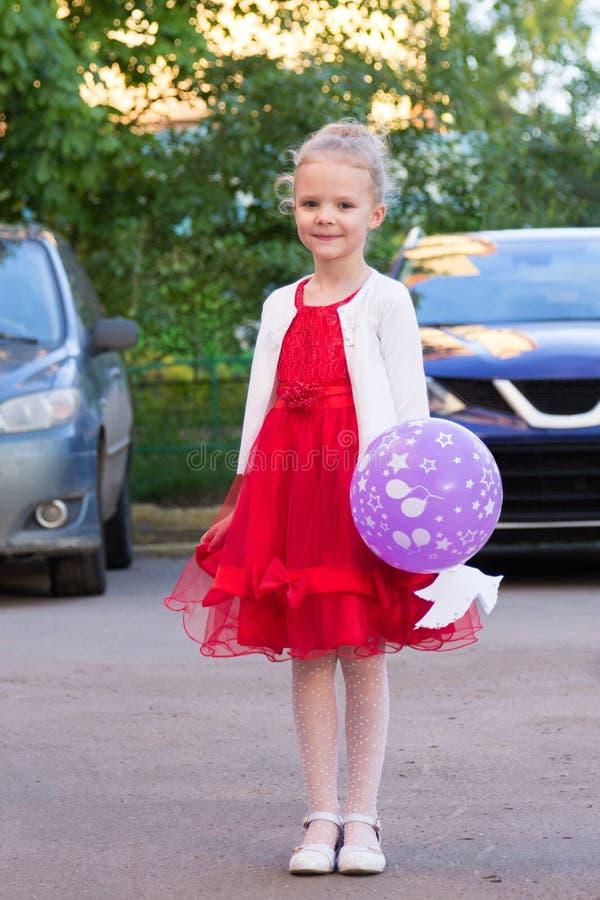 Leuk meisje in rode kleding met een ballon stock fotografie