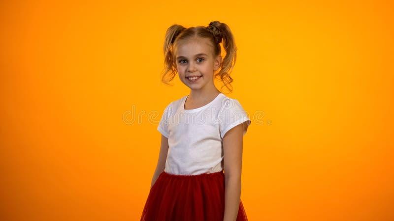 Leuk meisje in rode rok die en aan nok glimlachen kijken die op oranje achtergrond wordt geïsoleerd stock foto's