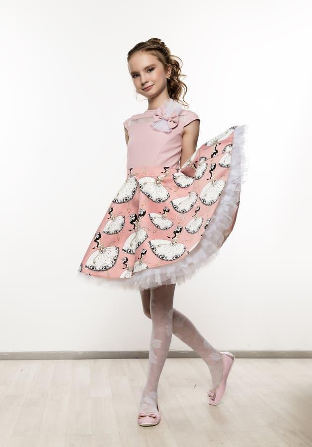 Leuk meisje in roze kleding op witte achtergrond De kinderen vormen, stijlconcept stock fotografie