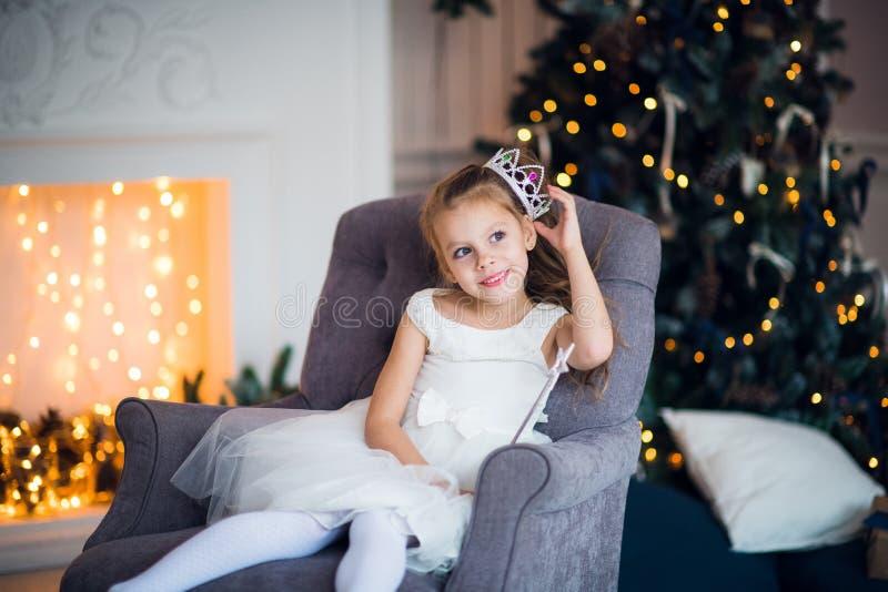 Leuk meisje in slimme witte kledingskerstmis rond de open haard die met vakantieslinger verfraaide stock afbeeldingen
