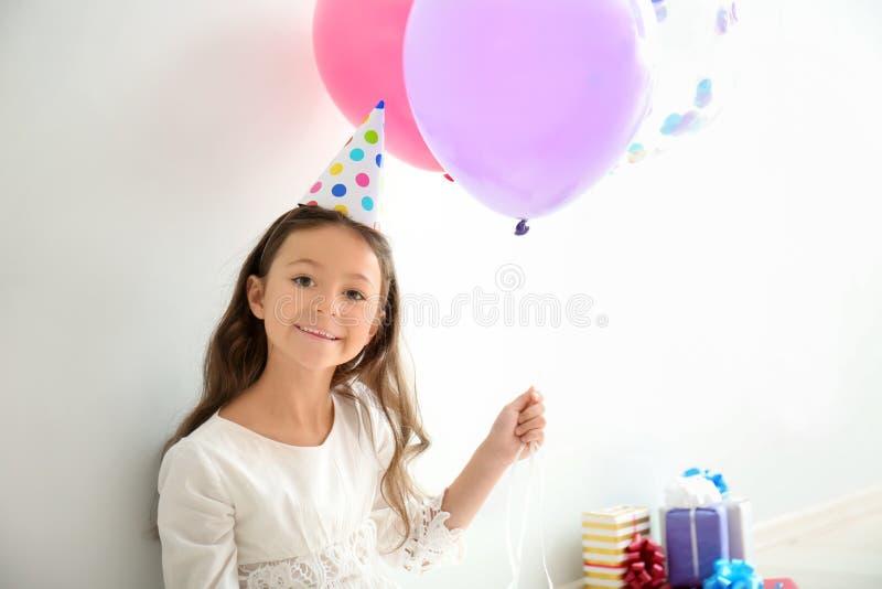 Leuk meisje in Verjaardagshoed en met ballons op lichte achtergrond stock foto's
