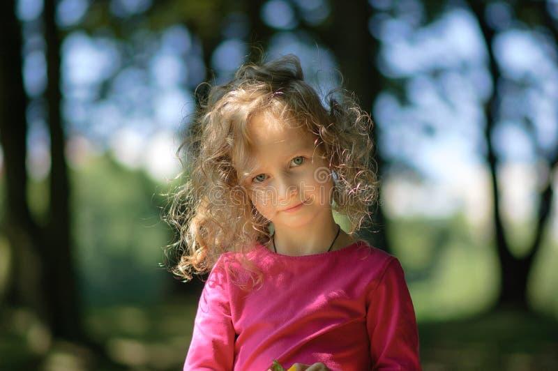 Leuk meisje, vrolijke blik, krullend haar, aardige glimlach, zonnig de zomerportret stock afbeeldingen