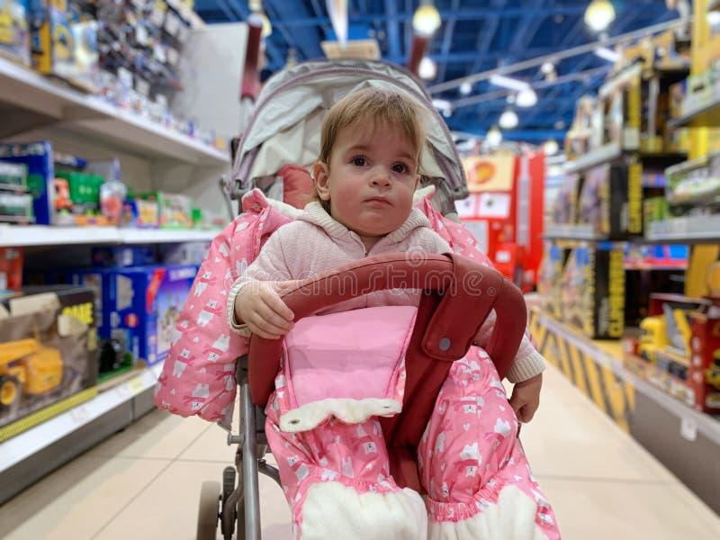 Leuk meisje in wandelwagen in speelgoedwinkel royalty-vrije stock afbeeldingen