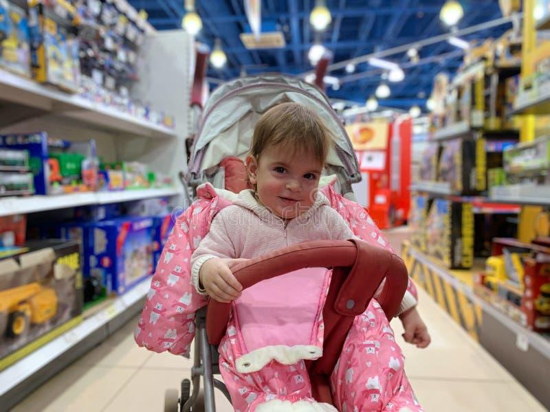 Leuk meisje in wandelwagen in speelgoedwinkel royalty-vrije stock foto's