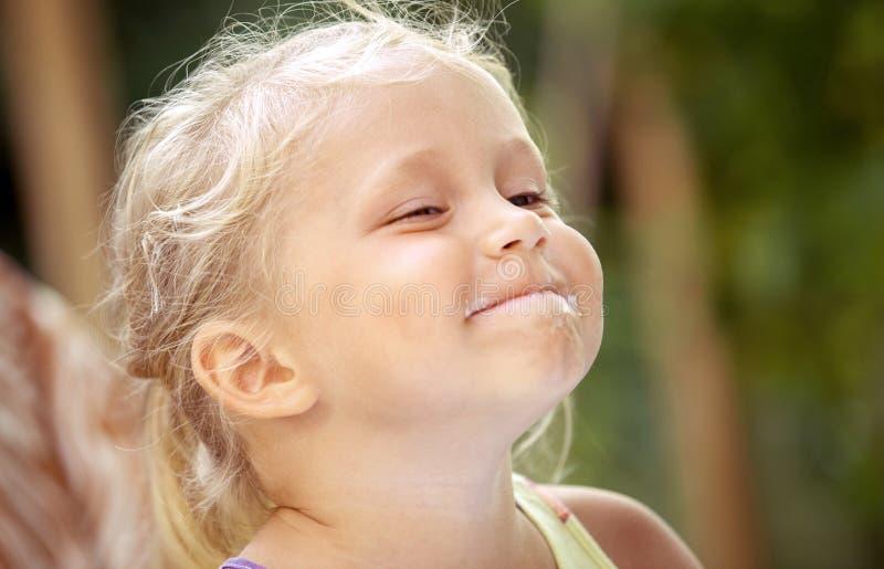 Leuk meisjekind met sporen van roomijs op haar gezicht op a royalty-vrije stock foto