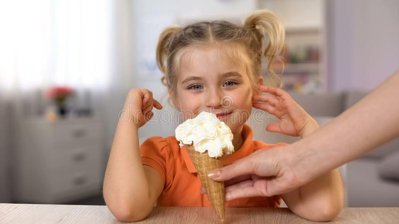 Leuk meisjes proevend ijshoorntje van vrouwelijke hand, kinderjarenverrassing, snack royalty-vrije stock afbeelding