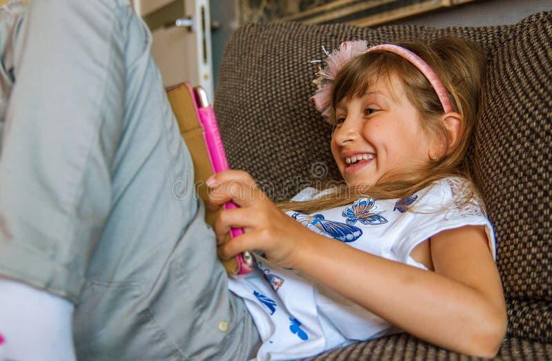 Leuk meisjesjong geitje gebruikend iPad digitale computertablet op bed voor onderwijs of spelend spel stock afbeeldingen