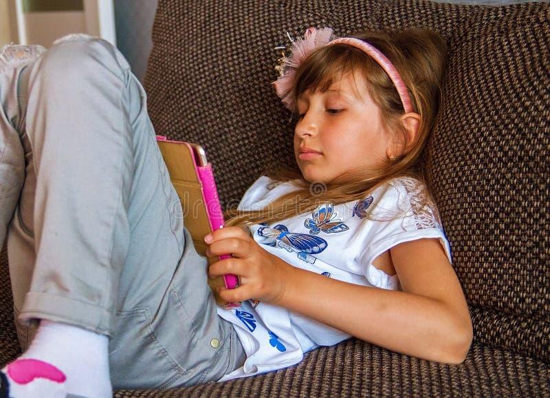 Leuk meisjesjong geitje gebruikend iPad digitale computertablet op bed voor onderwijs of spelend spel royalty-vrije stock foto's