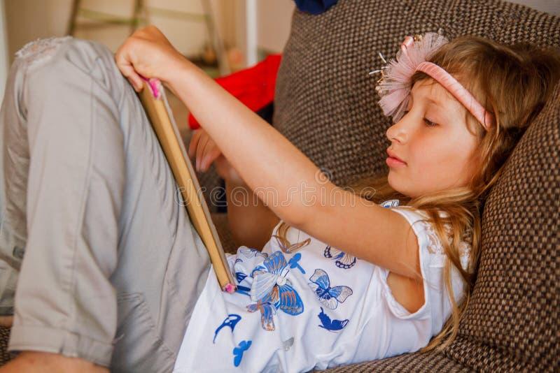 Leuk meisjesjong geitje gebruikend iPad digitale computertablet op bed voor onderwijs of spelend spel royalty-vrije stock afbeelding