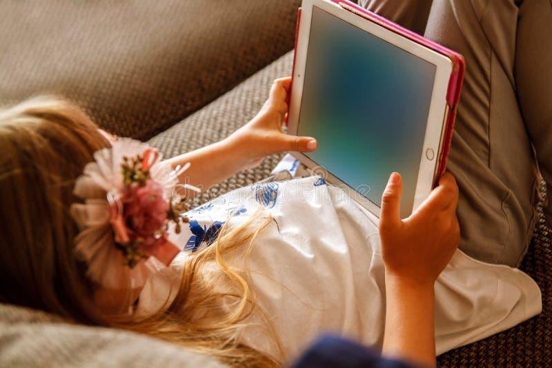 Leuk meisjesjong geitje gebruikend iPad digitale computertablet op bed voor onderwijs of spelend spel stock fotografie