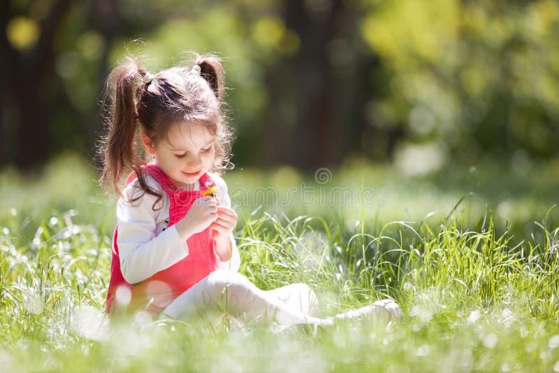 Leuk meisjespel in het park met bloemen De sc?ne van de schoonheidsaard met kleurrijke achtergrond bij de zomer of lentetijd stock afbeelding
