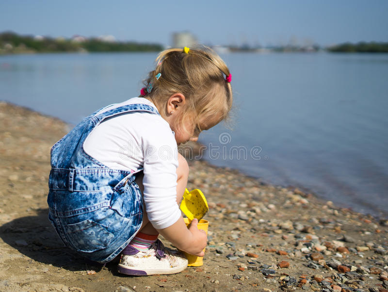 Leuk meisjespel met zand en schop op strand stock foto's