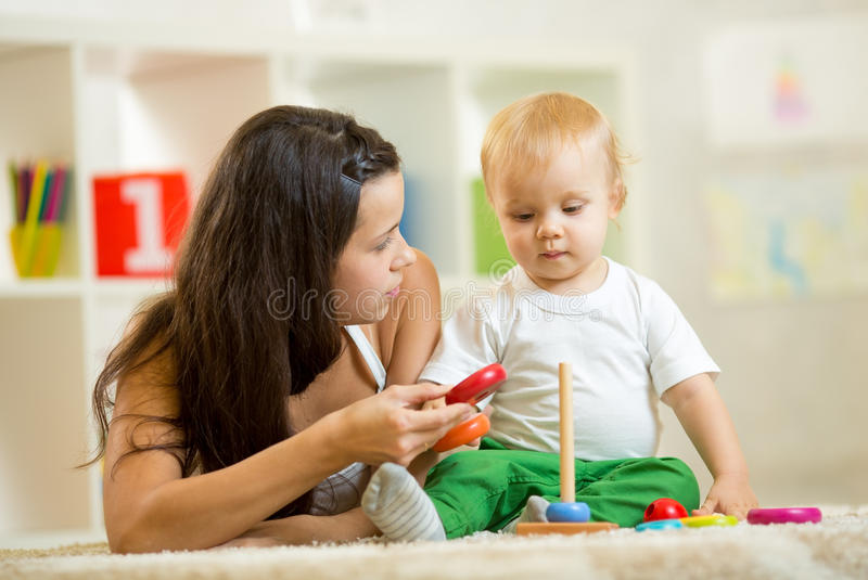 Leuk moeder en babyjongensspel samen binnen bij royalty-vrije stock afbeeldingen