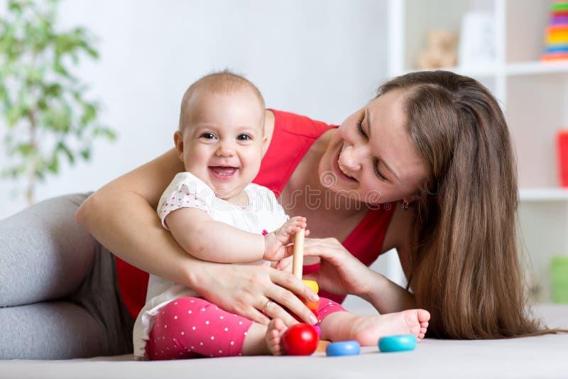 Leuk moeder en babyspel thuis binnen stock afbeeldingen